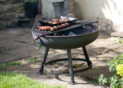 Classic fire pit with BBQ rack cooking in garden