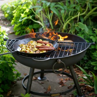 Half Moon Mesh BBQ Rack cooking food over fire pit