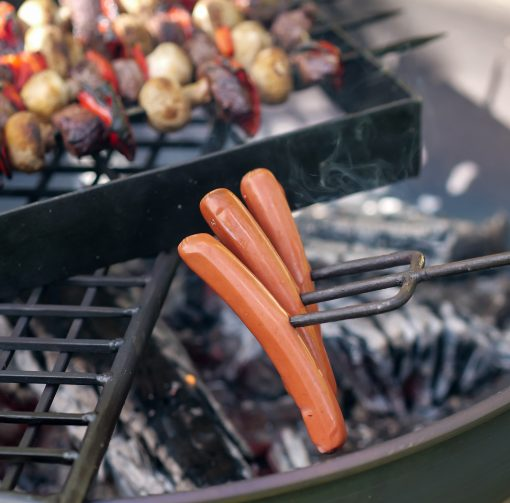 Toasting Fork with sausages on 3 prongs over fire pit