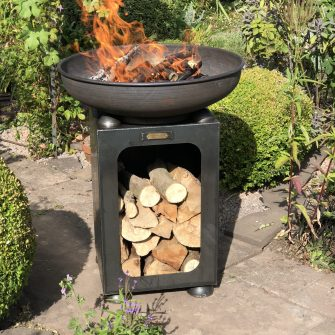 Fire Bowl with Log store lit in garden