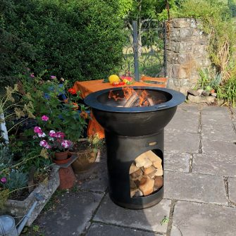 Planter Fire Pit with Log Store lit in garden