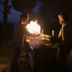 Asado BBQ with Log Store Lit Lifestyle at Night - Firepits UK - BBQ - Lo Res