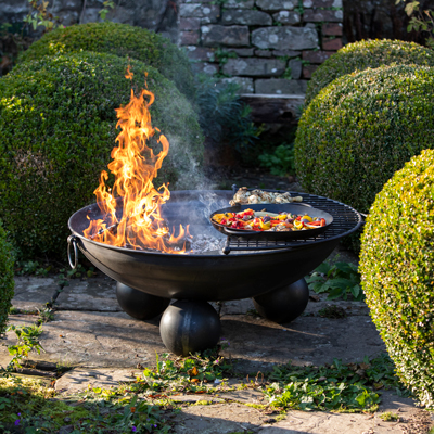 Ball Stand Fire Pit Lit with Half Moon BBQ Rack and Skillet Pan with Peppers Lifestyle - Firepits UK - WEB - Lo Res