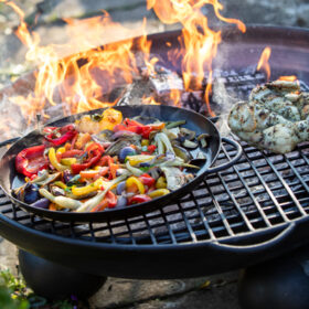 Ball Stand Fire Pit Lit with half Moon BBQ Rack and Skillet Pan with Peppers and Chicken Lifestyle - Firepits UK - WEB - Lo Res