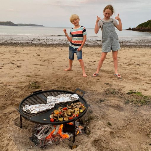 Beach BBQ Fire Pit Lit with Veg facing Sea Lifestyle - Firepits UK - WEB - Lo Res
