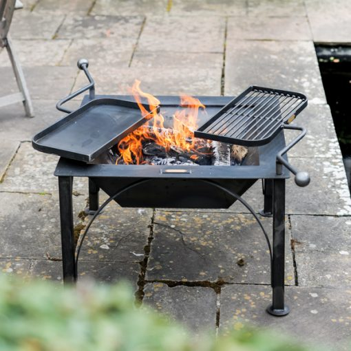 Box D Fire Pit with 2 Swing Arm BBQ Racks Lit Lifestyle on Patio - Firepits UK - WEB - Lo Res