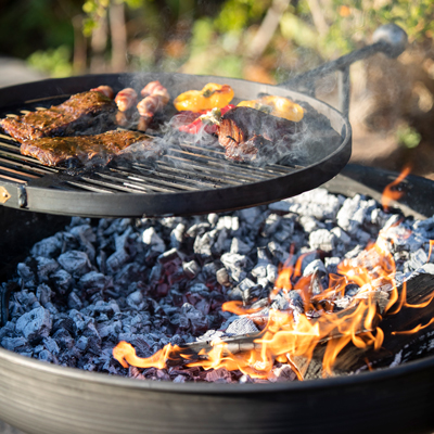 Legs Eleven Fire Pit Lit with Swing Arm BBQ Rack Close Up Lifestyle - Firepits UK - WEB - Lo Res.