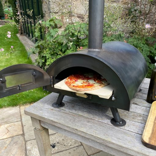 Table Top Pizza Oven Fire Pit with cooked pizza Lifestyle - Firepits UK - WEB - Lo Res2