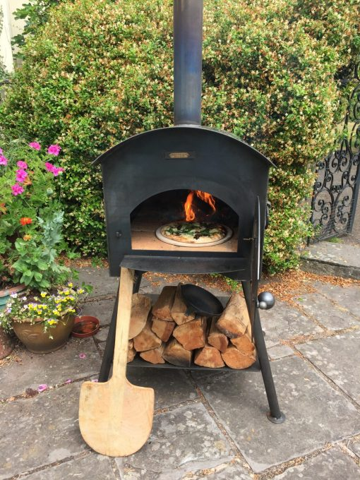 Traditional Pizza Oven Fire Pit Lit with Logs, Paddle and Pizza Lifestyle - Firepits UK - WEB - Lo Res