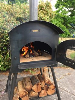 Traditional Pizza Oven Fire Pit Lit with Logs and Open Door Lifestyle - Firepits UK - WEB - Lo Res