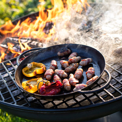 Wine Glass Fire Pit Lit with Half Moon BBQ Rack and Skillet Pan with Peppers and Pigs in Blankets Close Up Lifestyle - Firepits UK - WEB - Lo Res