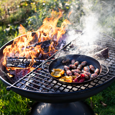 Wine Glass Fire Pit Lit with Half Moon BBQ Rack and Skillet Pan with Peppers and Pigs in Blankets Lifestyle - Firepits UK - WEB - Lo Res
